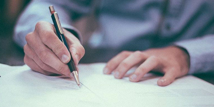man signs paper with a pen