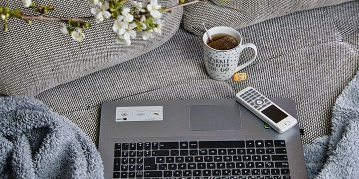laptop and cup of coffee on couch